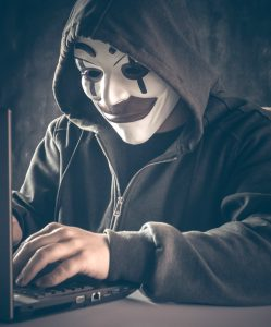 male hacker with anonymous clown mask in hoodie on laptop